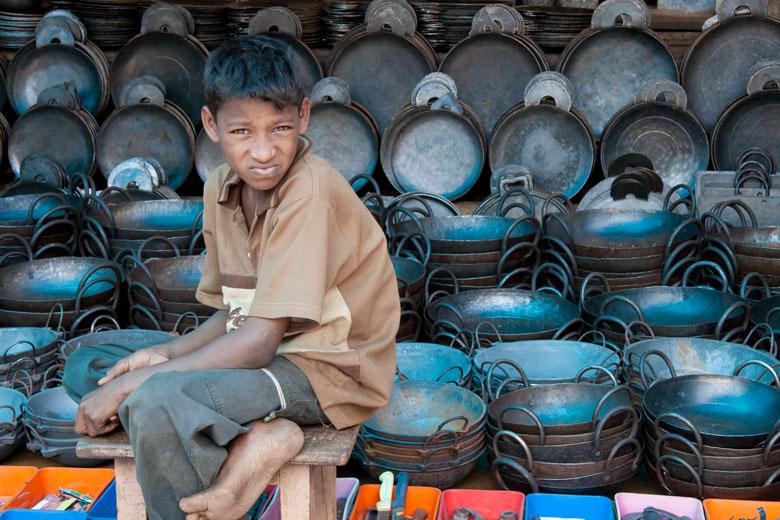 Kerala, India - ragazzo venditore in un tempio hindu